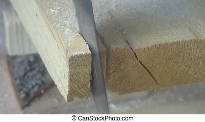 working with a handsaw sawing a wooden Board.