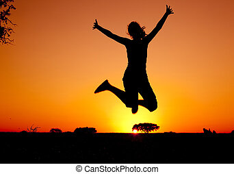 Jumping - Silhouette of a young woman jumping at the sunset