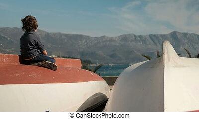 Little boy sitting on boat, looking far near sea outdoors....