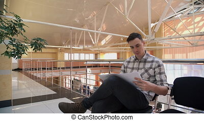 Man examine drawings sitting in hall in business center....