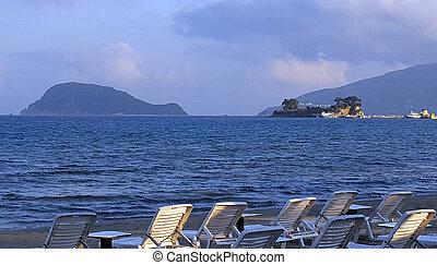 Beach chairs in Laganas beach with the Marathonisi Island...