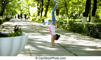 Little brunette girl doing somersault upheaval gymnastics in the park