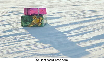Christmas gifts in a field on snow in a sunny, frosty and clear weather outdoors.