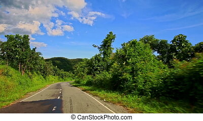 Motion along Curvy Road among Green Landscape past Car -...