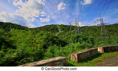 Camera Moves along Country Curvy Road among Hilly Landscape...