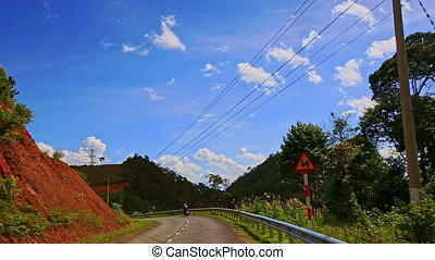 Camera Follows Scooter along Country Road among Hilly...