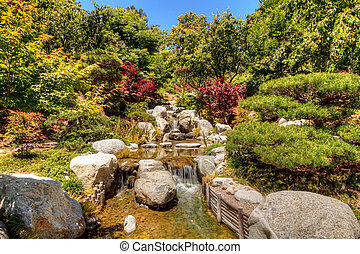 Relaxing, zen like pond with a waterfall, koi fish and...