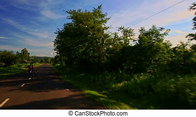 Camera Moves along Shady Sunny Road among Rural Landscape