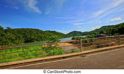 Camera Moves along Curvy Road past River among Landscape -...