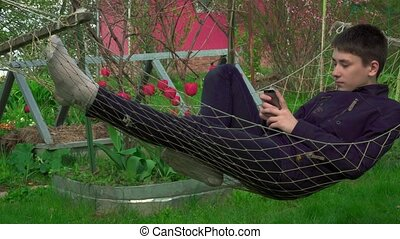 4K Portrait boy Playing Tablet in Hammock, the young man...