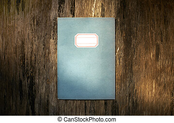 Classic notebook on wood plate in dramatic lighting