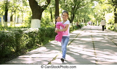 Little girl child brunette latin walking in the park with her toy doll