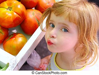 Hungry little girl gesturing in market tomatoes vegetables...
