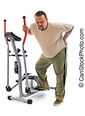 Man with back ache near a training device - Man holding his...