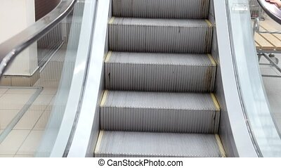 Escalator stairs in mall - moving staircase running up,...