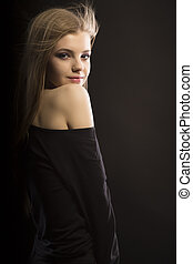Stylish young model with hair in motion at studio - Stylish...