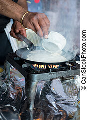 Hands pouring mixture to make dosa onto hot pan - Portrait...