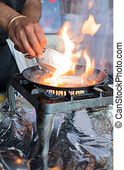 Flames on Hot Dosa Skillet on Stove - Flames rising from a...