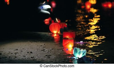 Floating lighting Lanterns on river at night - coast with lights