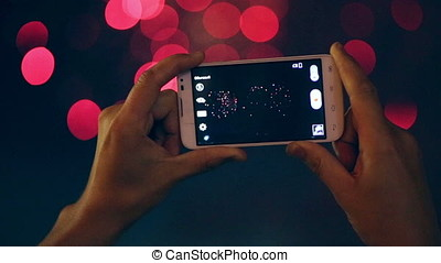 The fireworks are being recorded on the smartphone. - Two...