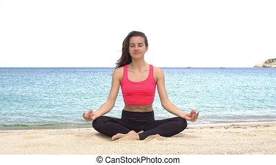 Young woman practicing yoga on the beach at sunset....
