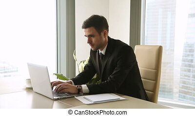 Young businessman finishing working day at office, all work...