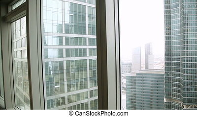 Successful young businessman coming to floor-to-ceiling window, looking at cityscape