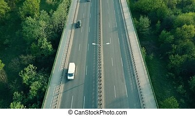 Aerial shot of cars, runner and cyclist moving along highway...