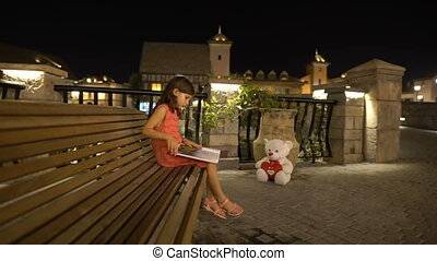 Little girl is reading book sitting on a bench