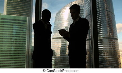 Two multicultural male colleagues discussing project,...
