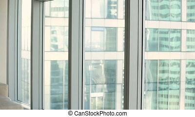 Pensive thoughtful young businesswoman standing near full length office window