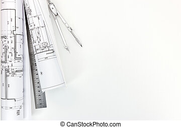 rolls of architectural blueprints and plans with measurement tools on architect workplace