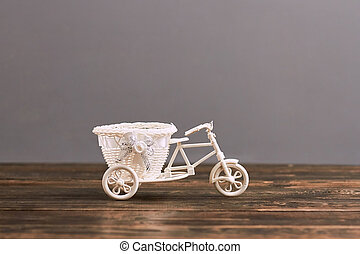 Small tricycle flower basket. Plastic toy on wooden surface....