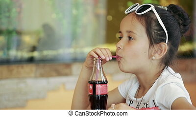 Little girl brunette latina sitting in cafe drinking soda cola Against the backdrop of an aquarium