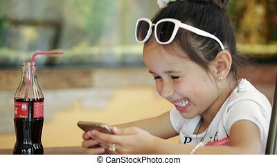 Little girl child brunette latina sitting in cafe, playing on smartphone in game smiling embarrassed