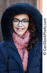 Smiling preteen girl wearing fur hood at winter