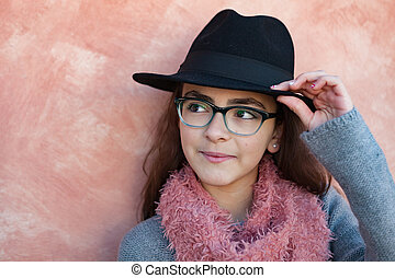 Smiling preteen girl wearing pink scarf and a black hat