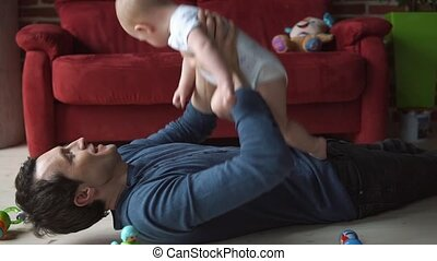 Father plays with little boy on the floor.