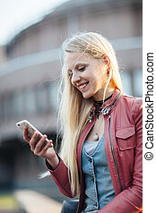 Happy blonde woman using her mobile phone in the street -...