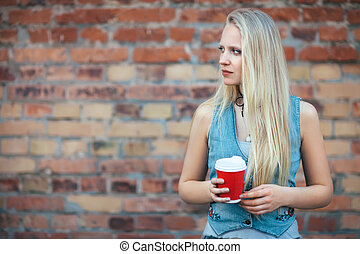 Beautiful blonde woman holding cup of coffee on brick wall...