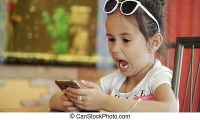 Little girl child brunette latina sitting in cafe, playing on smartphone in game, indignant, unhappy