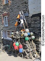 Lobster pots, buoys and marker flags next to a stone house...