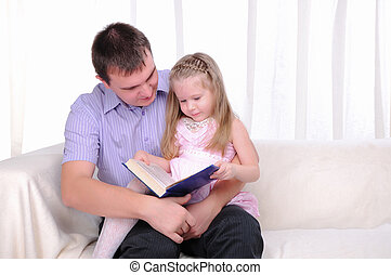 ittle girl is sitting on the lap of his father - The little...
