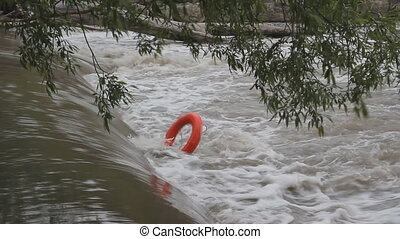 Lifering stuck in river. - Orange lifering stuck in a...