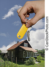 Home ownership - Hand holding a key in front of a house