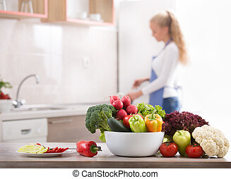 Fresh vegetables on table with woman in background -...