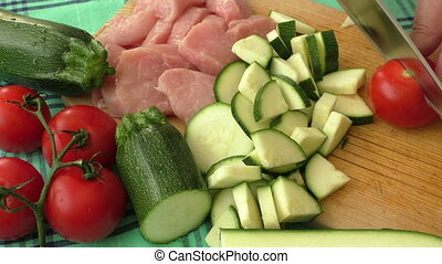 Fresh pork on the chopping board is cut into pieces with vegetables