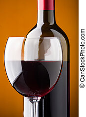 A bottle of red wine and a wine glass closeup