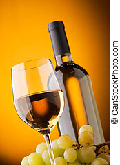 Bottom view of a glass of white wine bottle and grapes