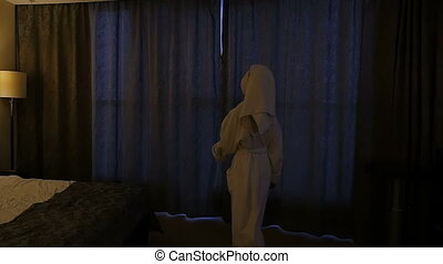 A young, beautiful woman in a white coat comes to the window, opens the curtains and looks at him. Slow motion
